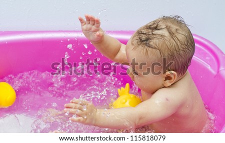 Portrait of happy baby while bath in bathtub with toys. - stock photo