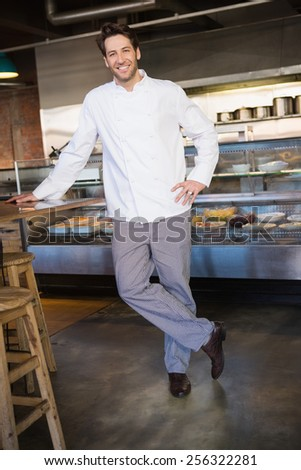 Portrait of happy baker leaning on counter at the bakery - stock photo