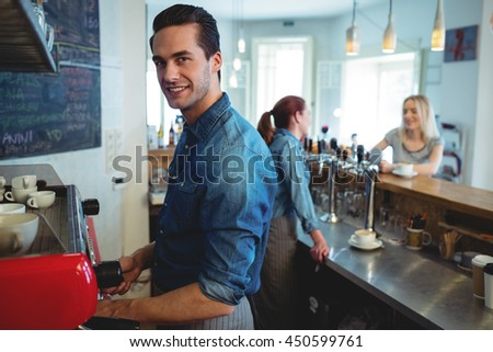 Portrait of happy barista while female colleague talking with customer at cafe - stock photo