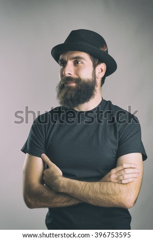 Portrait of happy bearded man with crossed arms looking away. Retro toned filtered portrait over gray background with vignette effect.