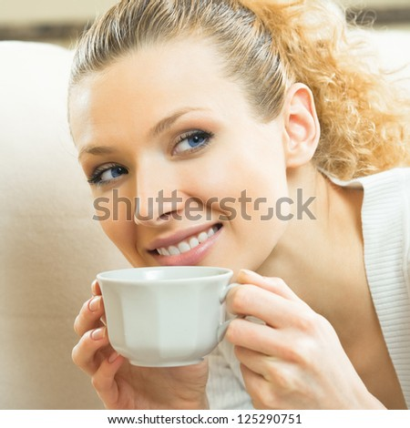 Portrait of happy beautiful blond woman drinking coffee or tea at home