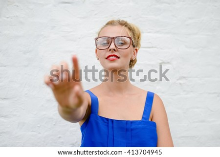 Portrait of happy beautiful blonde girl with hand in touching move, closeup on white background - stock photo