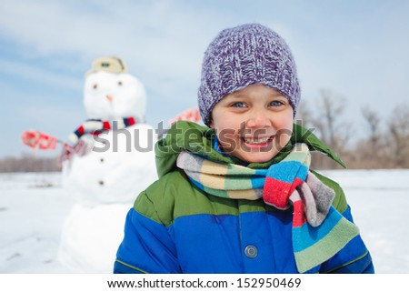 Portrait of happy beautiful boy with snowman outside in winter time - stock photo
