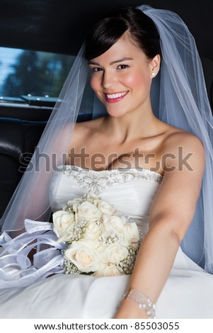 Portrait of happy beautiful bride in limousine - stock photo