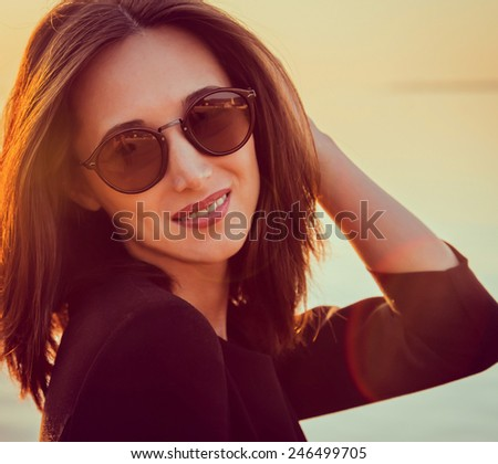 Portrait of happy beautiful brunette woman with long hair in sunglasses on background of sea at sunny day. Image with sunlight effect