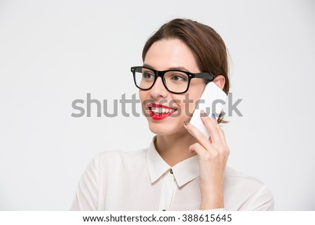 Portrait of happy beautiful business woman in glasses talking on mobile phone over white background - stock photo