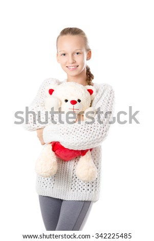 Portrait of happy beautiful casual caucasian teenage girl wearing knitted sweater hugging stuffed toy, friendly smiling, looking at camera with cheerful expression, studio image, white background - stock photo