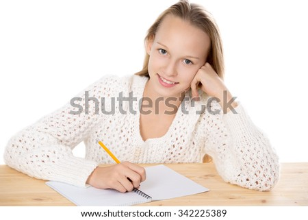 Portrait of happy beautiful casual girl wearing white knitted sweater, sitting at the table, doing homework, studying, writing in copybook, looking at camera, studio isolated, white background