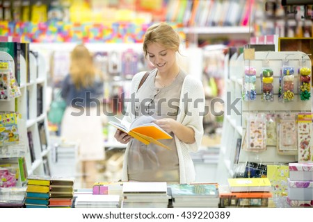 Portrait of happy beautiful caucasian person standing in bookstore and looking through books with a smile. Young smiling model wearing casual clothing choosing book in outlet during shopping time - stock photo