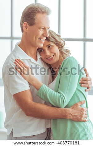 Portrait of happy beautiful couple in casual clothes cuddling and smiling - stock photo