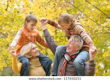portrait of happy beautiful elderly couple and grandchildren rest fall - stock photo