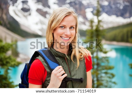 Portrait of happy beautiful female hiker smiling - stock photo