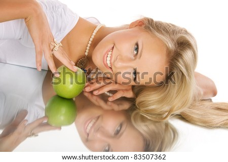 Portrait of happy beautiful girl and green apple, lying on mirror surface - stock photo