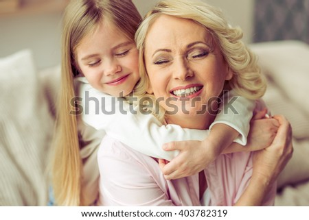 Portrait of happy beautiful granny and her granddaughter hugging and smiling while sitting with closed eyes - stock photo