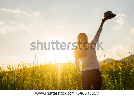 portrait of happy beautiful happy youngwoman relaxing in park. Joyful female model breathing fresh air outdoors and enjoying smell in a flower spring or summer garden, vintage tone.