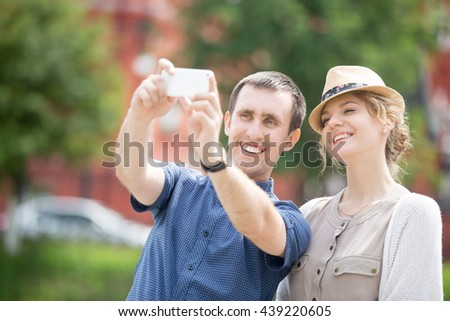 Portrait of happy beautiful travelers couple making selfie during abroad trip with smartphone. Attractive young traveling girl and guy taking pictures during sightseeing on overseas journey - stock photo