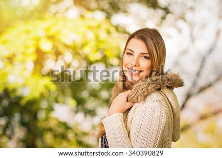 Portrait of happy beautiful young blonde Caucasian woman in beige knitted sweater in park in autumn. Gorgeous blond girl outdoors in fall. Horizontal, vibrant colors, medium retouch. - stock photo