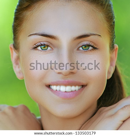 Portrait of happy beautiful young woman, against background of summer green park. - stock photo