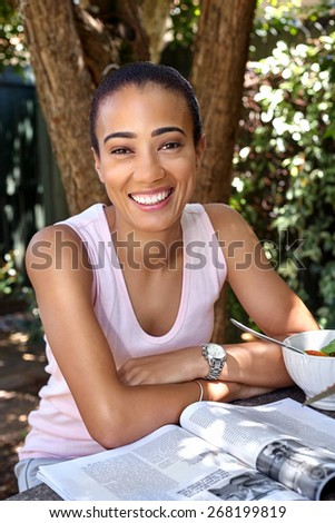 portrait of happy beautiful young woman with magazine sitting outdoors