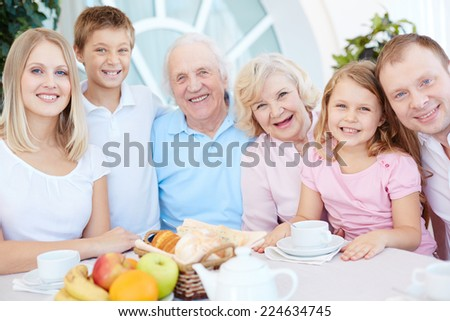 Portrait of happy big family of six having dinner at home - stock photo