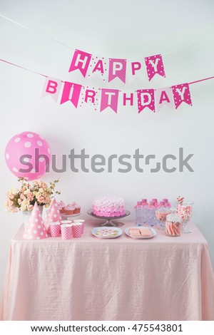 portrait of happy birthday flag banner chain and a table with full of sweet candy and cake