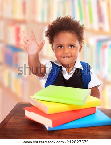 Portrait of happy black boy doing homework in the library, enjoying interesting literature, curious child, elementary school concept - stock photo