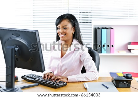 Portrait of happy black business woman at desk typing on computer - stock photo