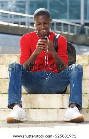 Portrait of happy black male student sitting outdoors and listening  music