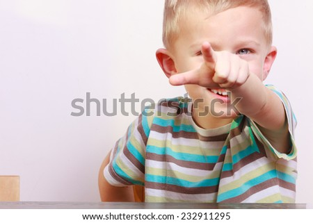 Portrait of happy blond cute boy child kid showing pointing at you at the table interior. Emotions. - stock photo