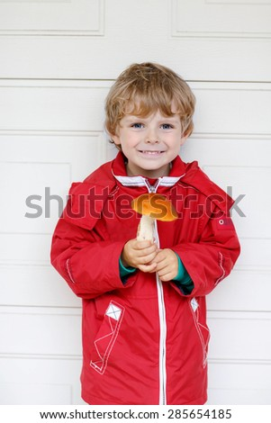 Portrait of happy blond little kid boy in red waterproof raincoat holding big mushroom in hands. - stock photo