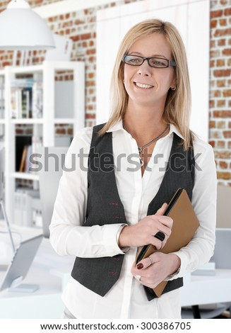Portrait of happy blonde businesswoman holding tablet, looking away.