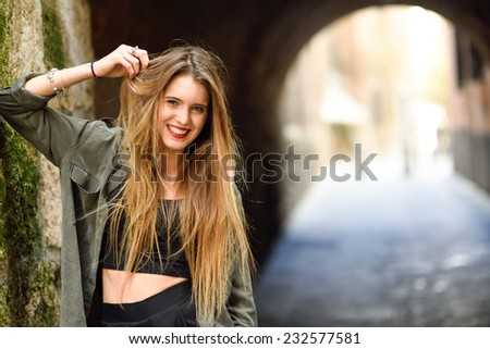 Portrait of happy blonde girl smiling in urban background - stock photo