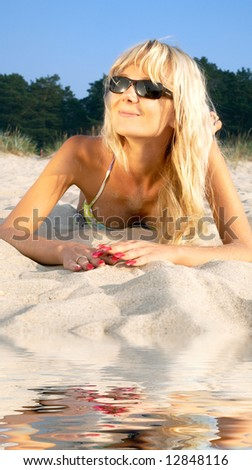portrait of happy blonde relaxing at the beach - stock photo