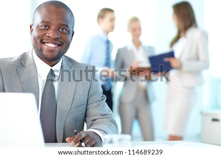 Portrait of happy boss looking at camera in working environment - stock photo