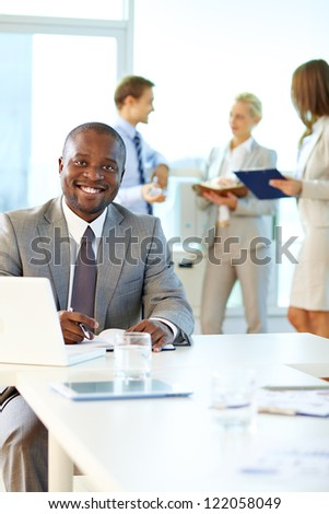 Portrait of happy boss looking at camera in working environment