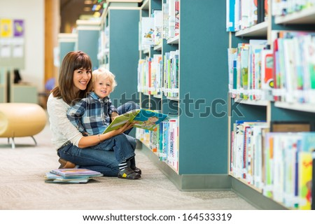 Portrait of happy boy and teacher reading book by bookshelf in library - stock photo