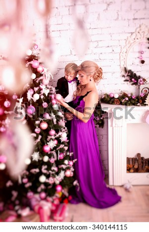 Portrait of happy boy  decorating Christmas tree.  Happy New Year. Portrait of happy mother and adorable baby - stock photo