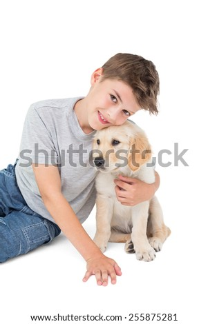 Portrait of happy boy embracing puppy over white background