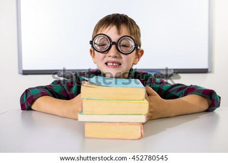 Portrait of happy boy holding books on table in classroom - stock photo