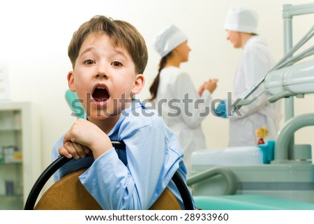 Portrait of happy boy in dentist room on background of two doctors - stock photo