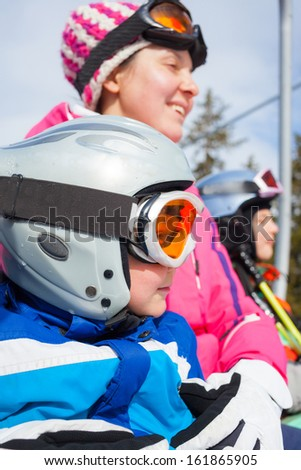 Portrait of happy boy in ski goggles and a helmet with his mother and sister on the ski lift - stock photo