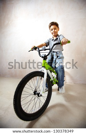 Portrait of happy boy on bicycle looking at camera - stock photo