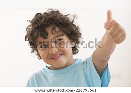 Portrait of happy boy showing thumbs up gesture, wearing blue t-shirt - stock photo