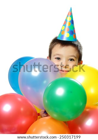 Portrait of happy boy with birthday cap and colorful balloons on white background - stock photo