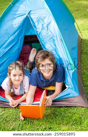 Portrait of happy boy with sister reading book in tent at park - stock photo