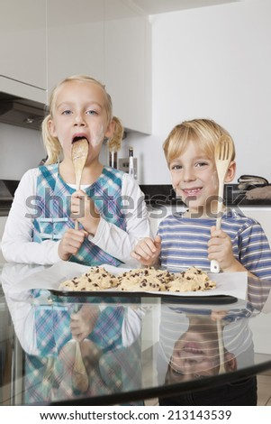 Portrait of happy boy with sister tasting spatula mix with cookie batter in kitchen - stock photo