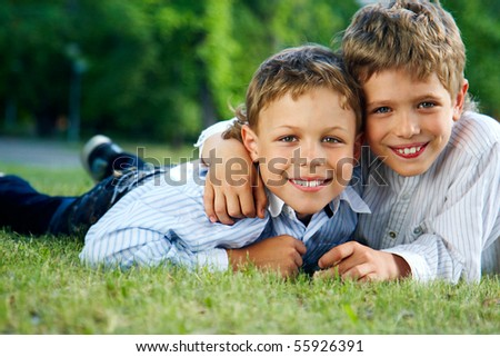 Portrait of happy boys lying on green grass and smiling at camera - stock photo