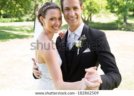 Portrait of happy bride and groom dancing together in garden - stock photo