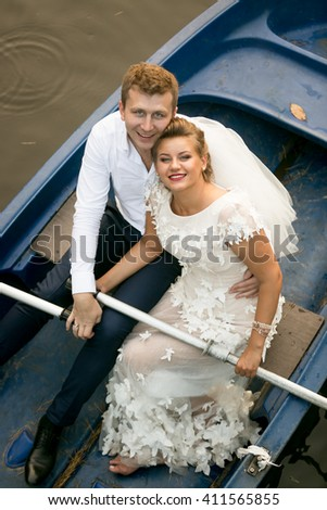 Portrait of happy bride and groom posing on rowing boat - stock photo