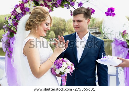 Portrait of happy bride putting golden ring on grooms hand at wedding ceremony - stock photo